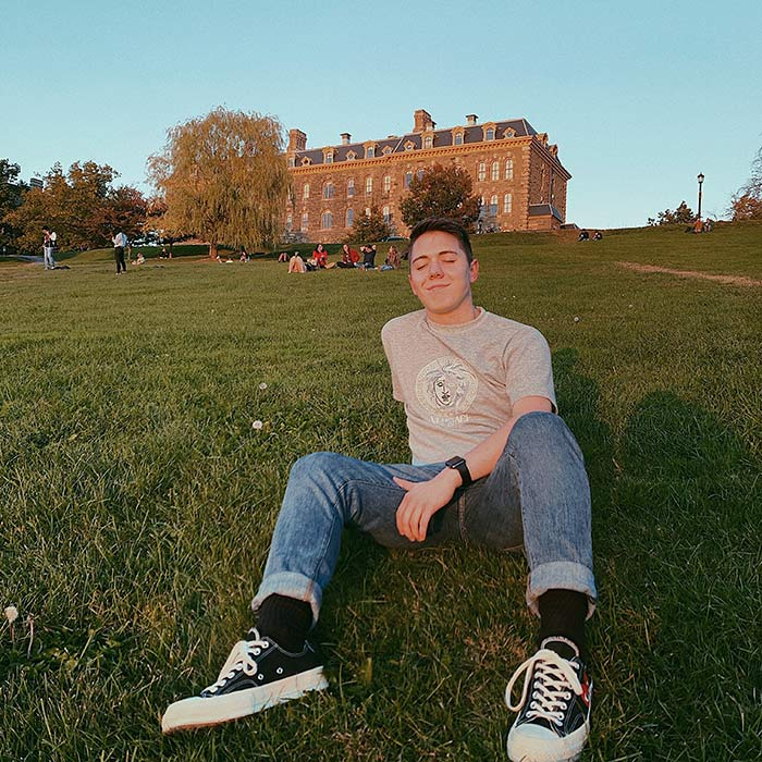 Clay sitting and enjoying the sunlight on a campus lawn