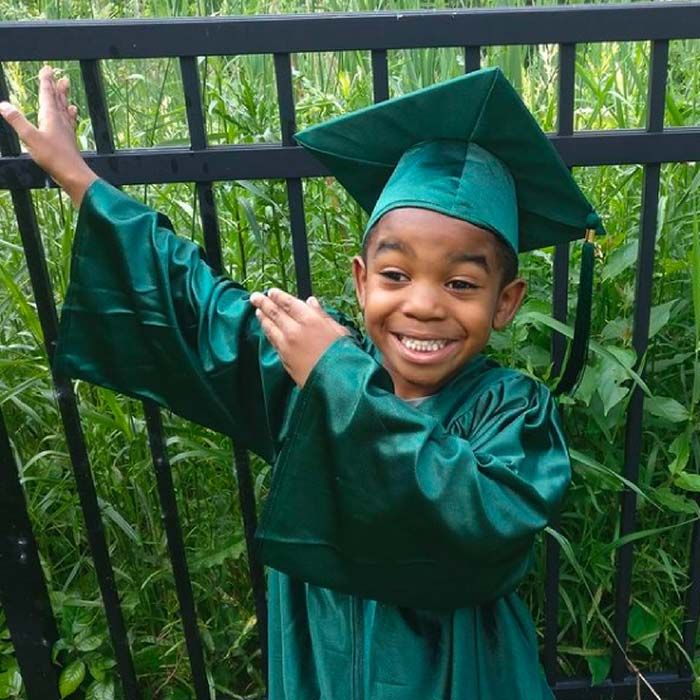 Dayna's son posing in a green elementary graduation outfit